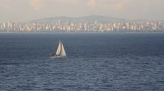 Small single masted sailing ship sails into Marmara Sea in Istanbul Stock Footage