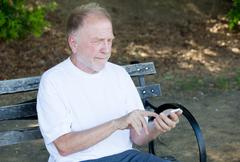 Closeup portrait of bold elderly man in white shirt, squinting, checking smar Stock Photos