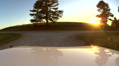 POV Jeep pulling out onto road with sun in horizon - stock footage
