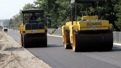 Stock Video Footage of Roadwork. Road rollers flattens asphalt. Steamrollers smoothing asphalt. Paving.