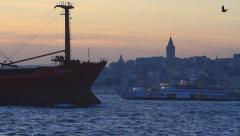 Large cargo ship sails past the city skyline Stock Footage