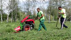 7. Mowers mowing the lawn. Cutting grass with lawnmower. Workers maintain park. - stock footage
