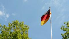 German (Federal Republic of Germany) flag - green trees - blue sky - sunny - stock footage