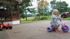 Two year old rides trike past leaf blower Stock Footage