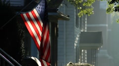American Flag, backlit, outside a house in a small town, hazy summer morning Stock Footage