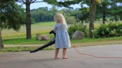Barefoot girl struggles to hold leaf blower - stock footage