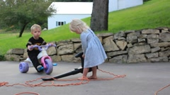 Little girl tries to run while carrying a leaf blower - stock footage