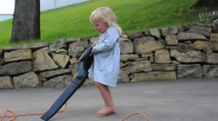 Little girl struggles with leaf blower - stock footage