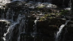 Small waterfall, gentle flowing water, dappled sunlight Stock Footage