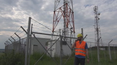 Engineer, electric transmission station, crash helmet and vest mobile phone talk Stock Footage