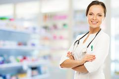 young positive brunette doctor woman in drug store - stock photo