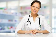 young positive brunette doctor woman behind table in drug store - stock photo