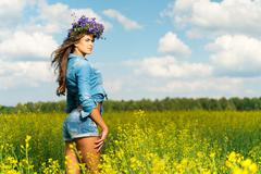 Beautiful young brunette in shorts and chaplet in a yellow field Stock Photos