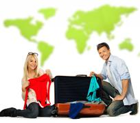 young couple packing suitcase for a journey against world map - stock photo