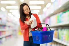 Beautiful brunette woman with basket reading label on cleanser in a shop Stock Photos
