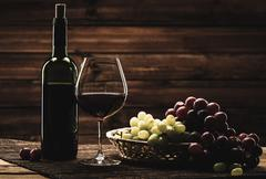 bottle of red wine, glass and grape in basket in wooden interior - stock photo