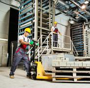 Young worker moving paving stones with pallet truck on a factory Stock Photos