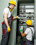 Two electricians in a safety hat and headphones on a factory Stock Photos