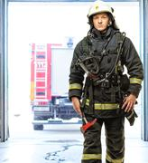 young firefighter against truck in firefighting depot - stock photo