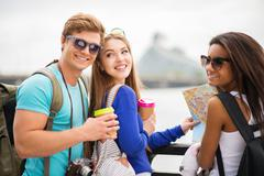 Multi-ethnic friends tourists with map and coffee cups near river in a city Stock Photos