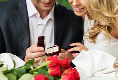 Man holding box with ring making propose to his girlfriend Stock Photos