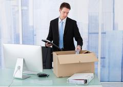 Young businessman collecting office supply in cardboard box at office desk Stock Photos
