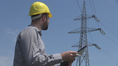 Stock Video Footage of Engineer at electric pole, taking notes on clipboard, analytical serious worker