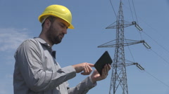 High voltage pole background, young man crash helmet on works on tablet, zooming Stock Footage