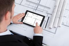 High angle view of male architect using digital tablet on blueprint in office Stock Photos