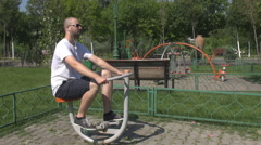 Cardio exercises for adult man outdoors, gym bike pushing pedals, stay fit daily Stock Footage