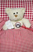 sick teddy bear lying in a red checked bed. concept for illness. - stock photo