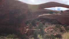 Pan of Landscape Arch, Arches National Park, blue sky, white clouds Stock Footage