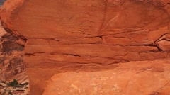 Pan to CU of natural red rock arch, Arches National Park, foreground soft focus Stock Footage