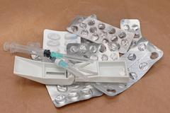 Pile of used medication blisters and syringes Stock Photos