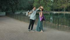 young couple having fun in a park making jokes after shopping: shopping bag - stock footage