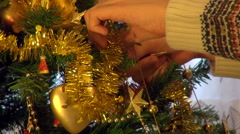 Young man hands garnishing Christmas tree, golden decorations, close up Stock Footage