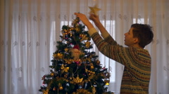 Teenage boy puts golden star on top of Christmas tree, decorations, holiday Stock Footage