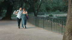 young couple having fun in a park making jokes after shopping - stock footage