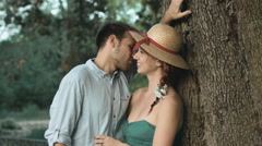 Young couple in love kissing near a tree: date, outdoor, kiss, partners Stock Footage