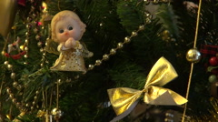 Golden angel, beads and bow in Christmas tree, red lights, holiday season Stock Footage