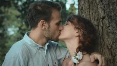 Young couple talking and kissing near a tree in a public garden: park, outdoor Stock Footage