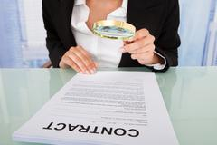 Midsection of businesswoman scrutinizing contract with magnifying glass at of Stock Photos