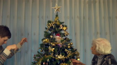 Grandmother and grandson decorating Christmas tree, family, holiday, season Stock Footage