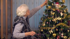 80 years old woman decorating Christmas tree, grandmother, holiday Stock Footage