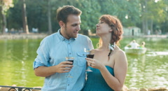 Young man and girl drinking whine inside a public park near romantic lake Stock Footage