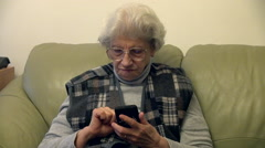 80 years old woman using smart phone,cellphone,grandma,reflection in eyeglasses Stock Footage