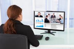 Rear view of businesswoman video conferencing with team on computer at desk i Kuvituskuvat