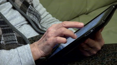 Old woman hands using tablet computer, playing games, close up Stock Footage