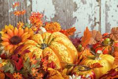 Autumn display with a squash surrounded by decorative gourds and flowers - stock photo