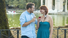 young couple kissing and drinking near small lake in a  garden: romantic date - stock footage